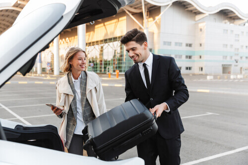 chauffeur helping customer with luggage